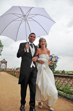 Wedding Couple walking at Kenilworth Castle in the rain